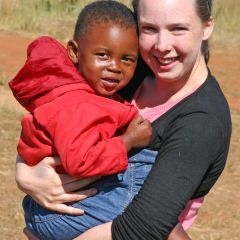 Volunteer hugging orphaned child