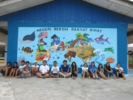 Volunteers with their mural painting for the local school