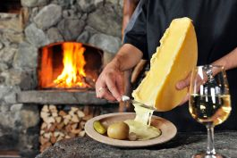 Enjoy traditional Swiss raclette and local wine by a roaring log fire